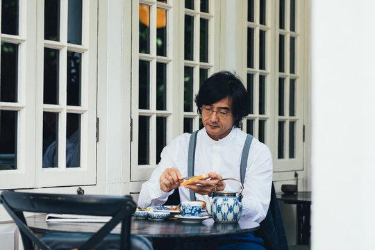 Middle-aged Asian man having breakfast on a terrace.