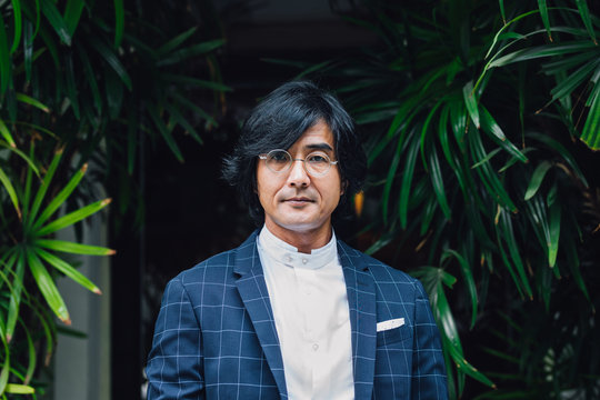 Portrait of elegant Asian middle-aged businessman standing outdoors and looking at camera.