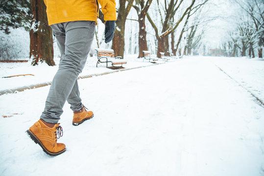 man walking by snowed winter city park legs close up concept