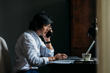 Serious middle-aged Asian businessman working at his office and talking on his smart phone.