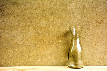 alone glass vase on wood desk in cement kitchen room at the morning - high contrast background