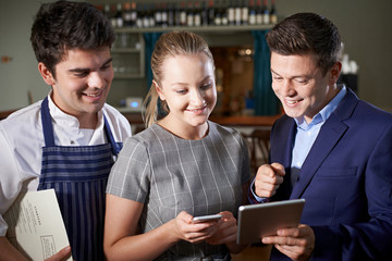 Restaurant Team Discussing Menu Looking At Digital Tablet