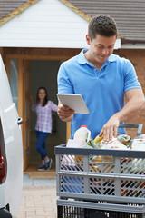 Driver Delivering Online Grocery Order To House Using Digital Tablet