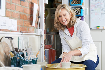 Portrait Of Mature Woman Working At Potters Wheel In Studio