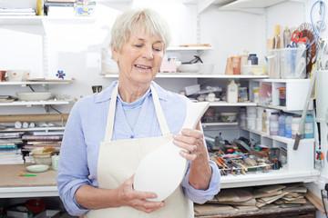 Senior Woman Holding Vase In Pottery Studio