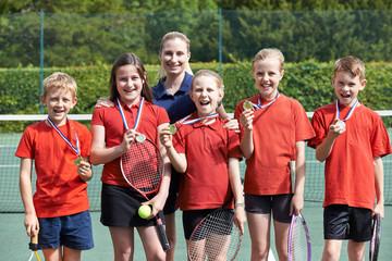 Portrait Of Winning School Tennis Team With Medals