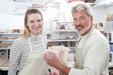 Portrait Of Mature Man With Teacher Looking At Vase In Pottery Class