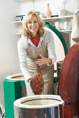 Portrait Of Mature Woman In Pottery Studio Firing Vase In Kiln