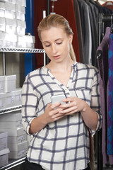 Businesswoman Running On Line Fashion Business In Warehouse Using Mobile Phone