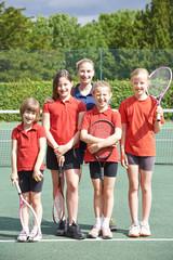 Portrait Of Female School Tennis Team With Coach