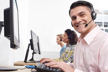 Portrait Of Male Customer Services Agent In Call Centre