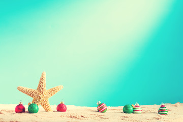 Starfish with Christmas ornaments on a beach sand