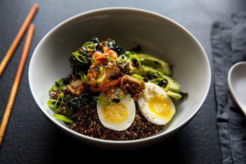 Close up of mixed grain bowl with kale, kimchi, and egg served in bowl
