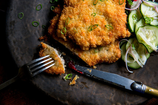 Close up of pork schnitzel served on a plate with pickled veggies