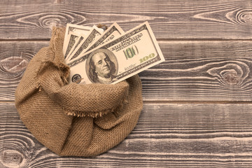 American dollar bills in a bag of burlap on a wooden table background. business, Finance, capital investment.
