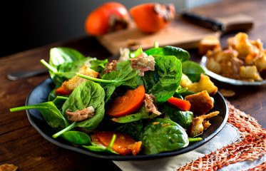 Spinach salad with prosciutto, persimmon and parmesan croutons served on plate