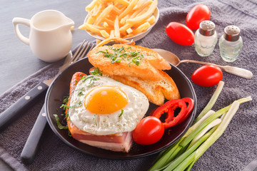 Aluminium Prints Egg Fried egg with bacon in a black plate with fried pieces of bread, greens tomatoes, a jug of milk and French fries on a gray wooden table. Close-up