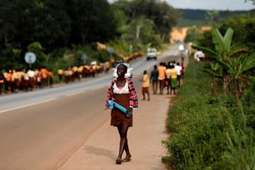 A girl reacts as she watches schoolchildren walking home near Princess town