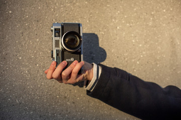 Happy young hipster woman holds retro photo camera. Close-up