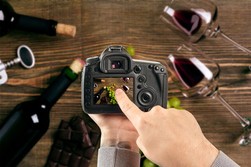 Digital single-lens reflex camera in hands. Man photographer makes photos. Male hands hold the camera close-up