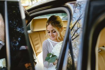 A bride takes pictures in the black car.