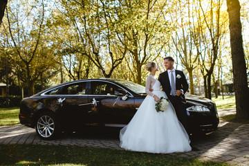 Bride and groom take photos near a black car.
