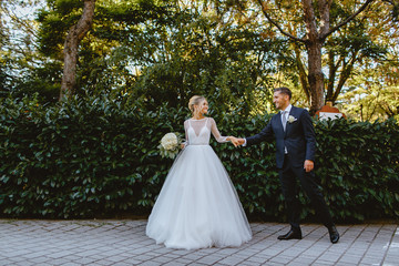 Bride and groom walk through the park in the city of Ravenna.