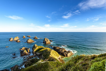 Stunning landscape at Nugget Point, one of the most distinctive spots on the Otago coast of New Zealand. It features a steep headland with a lighthouse and a dozens of rocky islets.