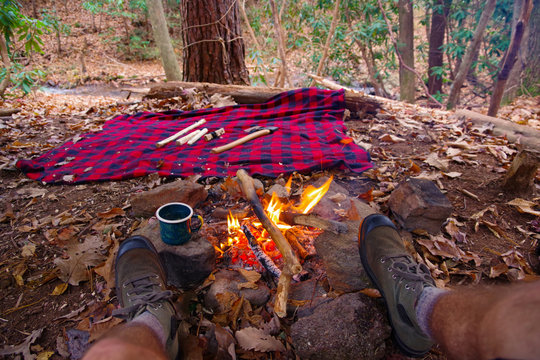 First person view of man relaxing / having tea in an enamel outdoor mug by a campfire in Blue Ridge / Appalachian Mountains trail near Asheville, North Carolina. Boots, Bushcraft, blanket, Axe.