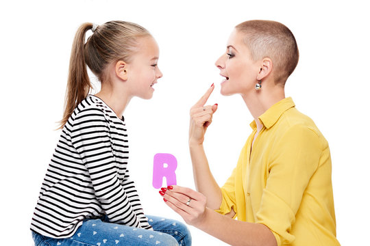 Cute young girl with speech therapist practicing correct pronunciation. Child speech therapy concept on white background. Speech impediment corrective exercises.
