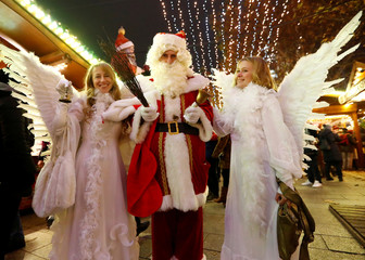 A man dressed as Santa Claus poses for a picture with women dressed as angels at the site of the Christmas market's truck attack, which killed 12 people and injured many others two years ago, at Breitscheidplatz square in Berlin