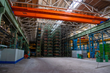 The interior of a large warehouse of heavy iron products and metal goods with pallet storage shelves at a production forge plant. Rows of shelves in commercial factory Industrial plant in Belarus