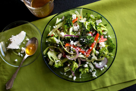 Overhead view of pre summer Greek salad with shaved broccoli in bowl