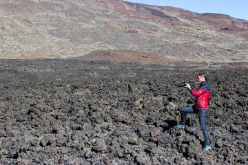 Photographer and traveller taking a picture of volcanic lava stones standing on clinker field near mountains