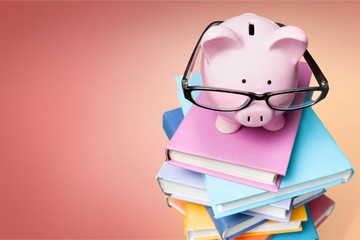 Piggy bank in glasses and books on background