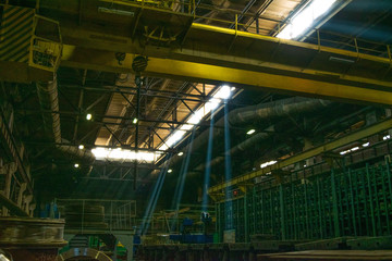 Rays of light in a dark industrial workshop of an industrial plant. Warehouse of heavy iron and metal