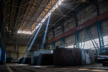 Rays of light in a dark industrial workshop of an industrial plant. Warehouse of heavy iron and metal. Machine shop of metallurgical works indoors room.
