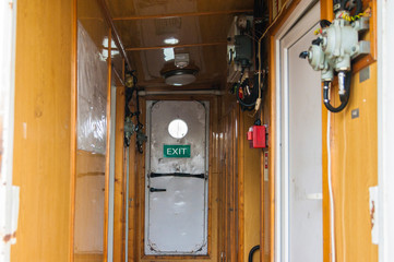 White door with a porthole aboard in the cabin.