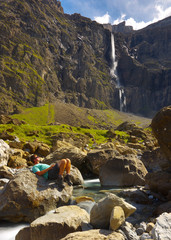 Resting tourist sitting on the big stone with a high waterfall on bacground, valley of Gavarnie, Pyrenees Occidentales, France