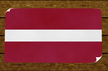 Illustration of a  Latvian flag painted on the papier pasted on the woody wall