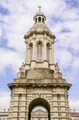 Ornate bell tower under blue sky and puffy white clouds - The Trinity College Campanile in Dublin, Ireland with the Regent House roof and clock centered in the arch of the tower
