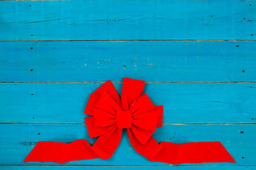 Blank rustic antique teal blue wood sign with red Christmas bow border; holiday background with painted wooden copy space