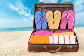Retro suitcase with travel objects  on sea background