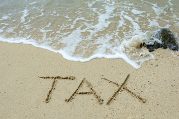 Tax text written on the sand beach, financial concept