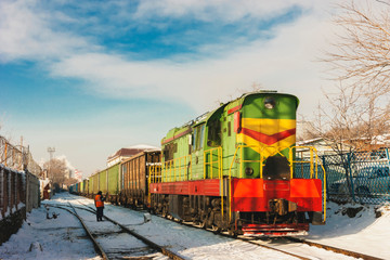 Freight green train rides by rail near the cargo port.