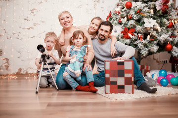 Image of happy family sitting with gift box at decorated Christmas tree