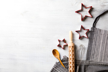 Kitchen apron on Holiday Background Concept of Christmas and New Year. Festive  Baking. Poster design, rolling and whisk, a wooden spoon and cookie cutters and gingerbread. Copy space for Text.