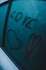 Love title and symbol of heart on car window