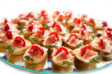 Close up of small canapes arranged on a plate over light background - selective focus