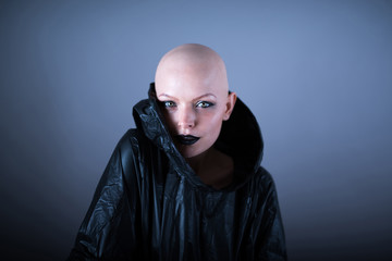 Emotive photo of a beautiful bald woman while standing in the studio and wearing a black raincoat.